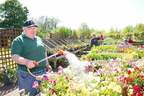 Disabled man watering flowers outside in North Yorkshire.