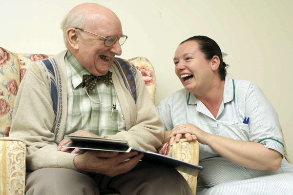 Older man laughing with care worker in North Yorkshire.