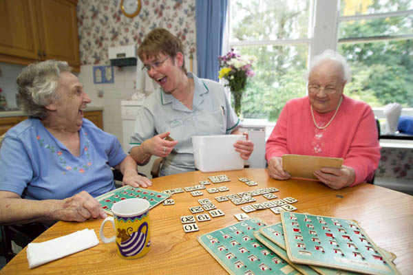 Older women playing a game with a care worker in North Yorkshire.