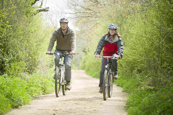 Man and woman riding bikes on a path in North Yorkshire.