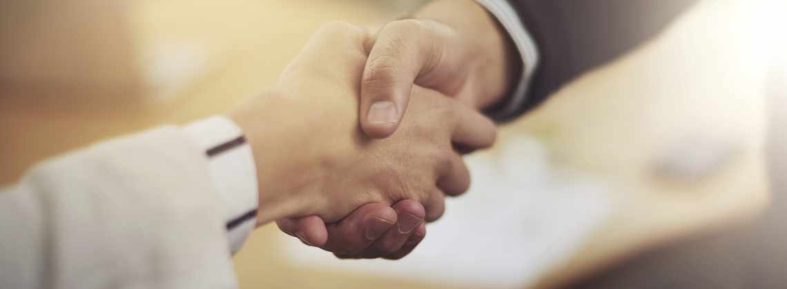 Two senior business partners shaking hands