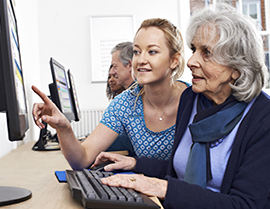 Older lady being shown how to use an online service.
