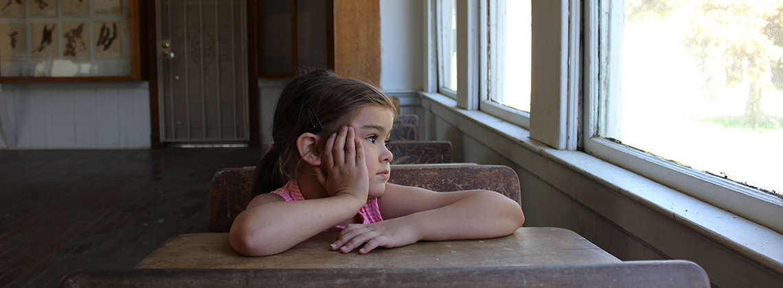 Child at a desk, looking out of a school window.