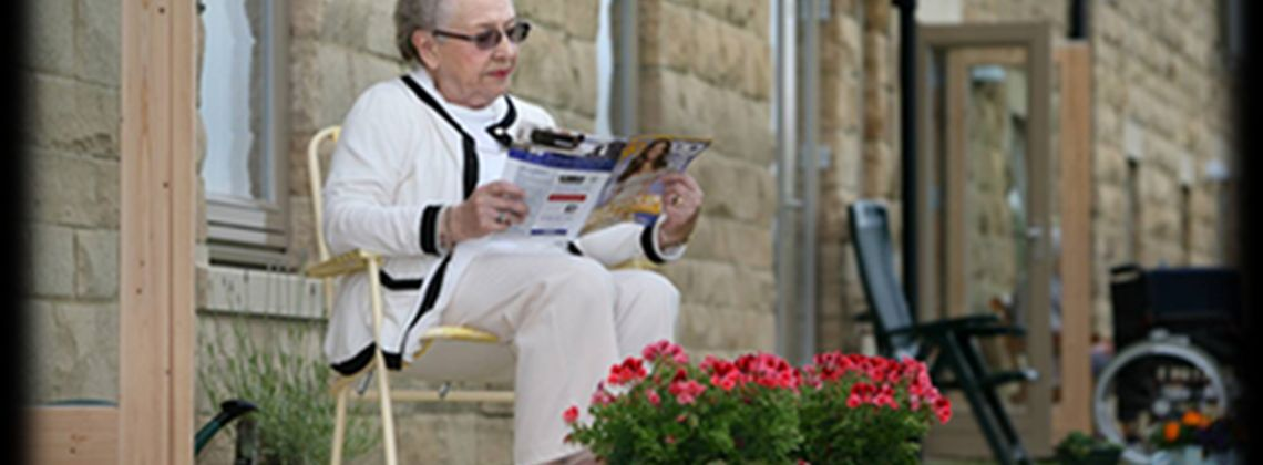 old lady reading in garden