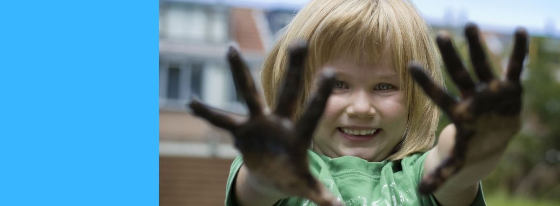 Young child holding up muddy hands