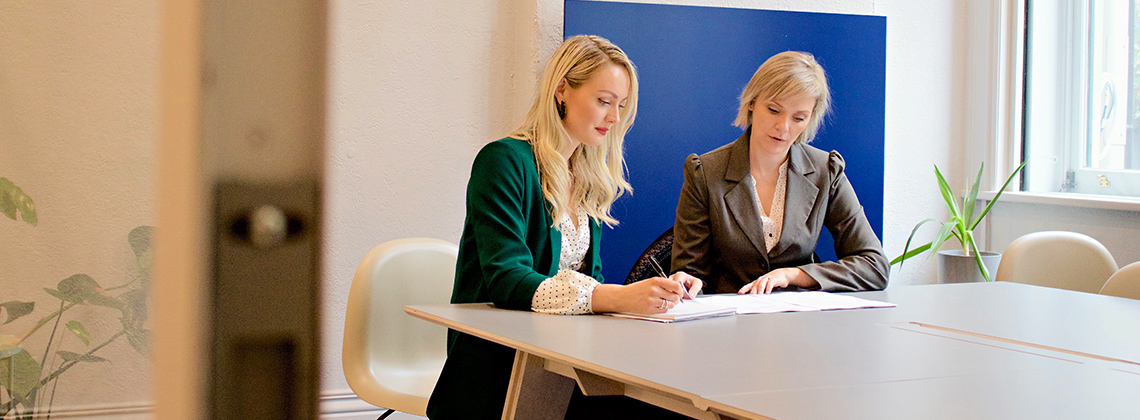Two women signing legal documents