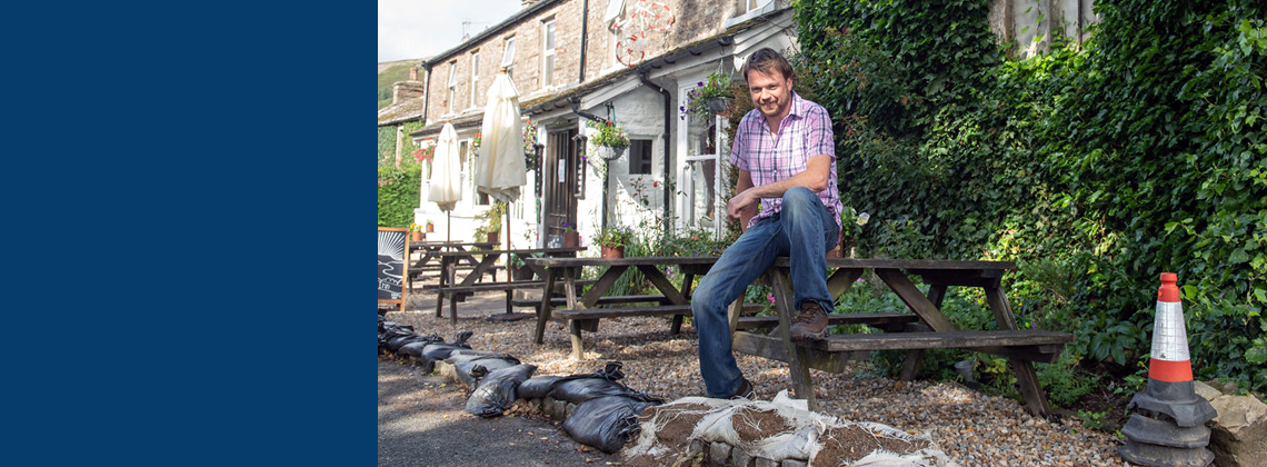 A man outside a pub that was affected by flooding.