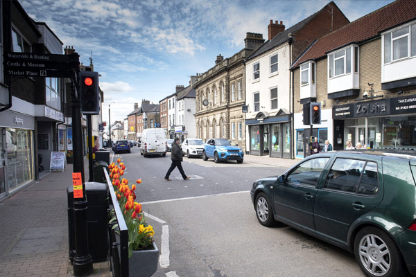 Person crossing road with car waiting in Knaresborough in North Yorkshire