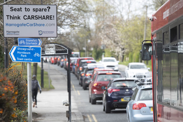 Car share sign in Harrogate with traffic next to it.