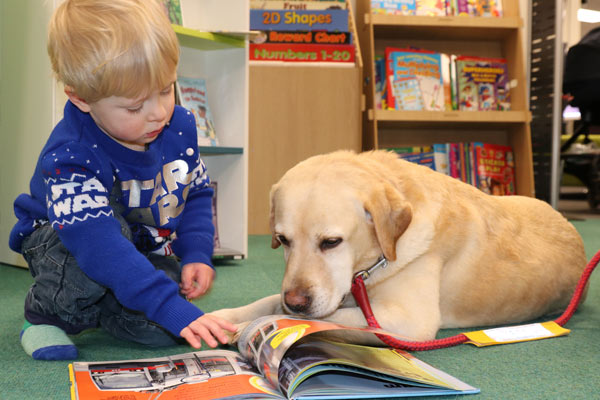 Child reading to a dog in Selby Library for the Read2Dogs campaign