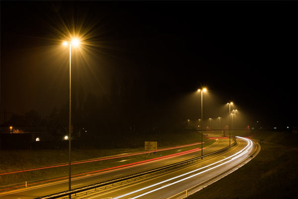 Row of street lights at night causing carbon emissions