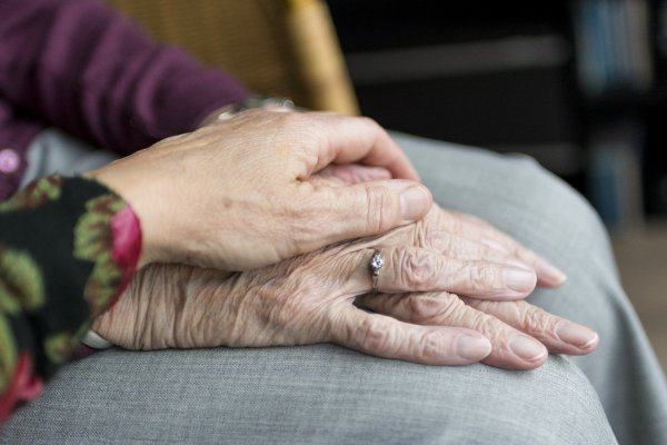 A hand on the hand of an elderly person.