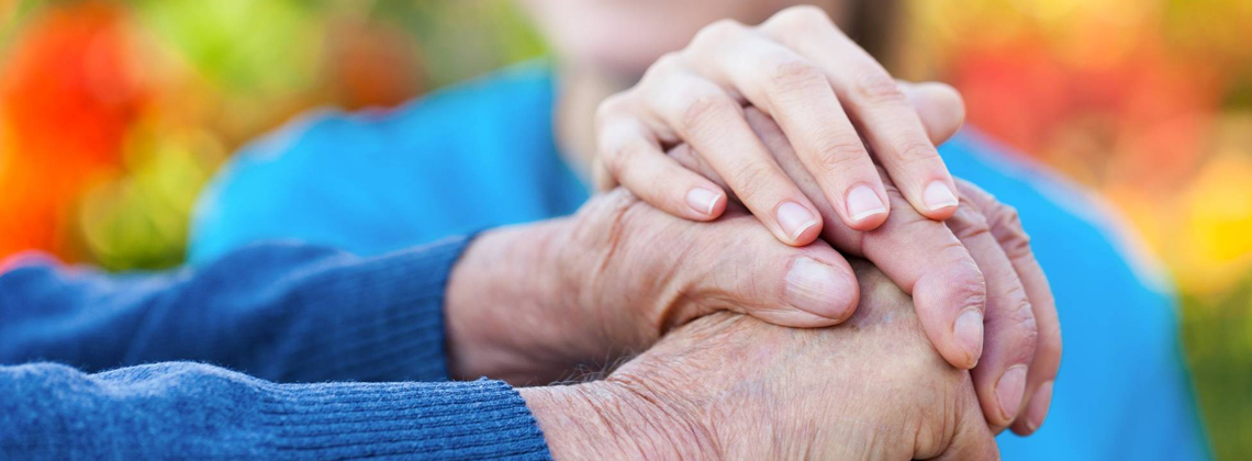 Two hands of an elderly person with a young person's hand on top of them.