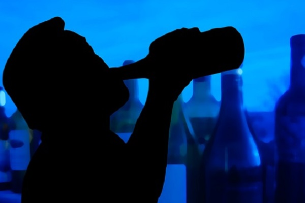 Silhouette of a man drinking from a bottle in front of other alcoholic drinks to illustrate alcoholism in North Yorkshire.
