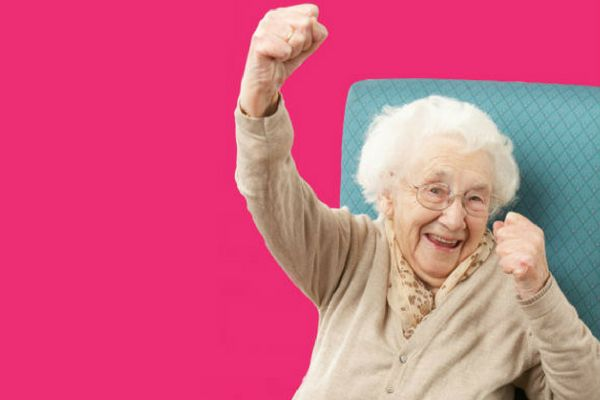 Elderly Lady celebrating adult care, cheering with her arm in the air.