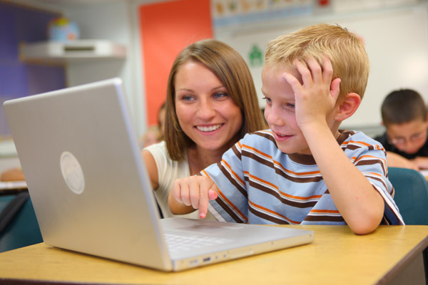 Primary school child and teacher using laptop