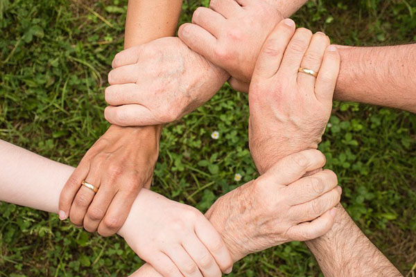 Six hands holding each other in a spirit of partnership.
