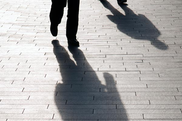 shadow of youths walking down a street.