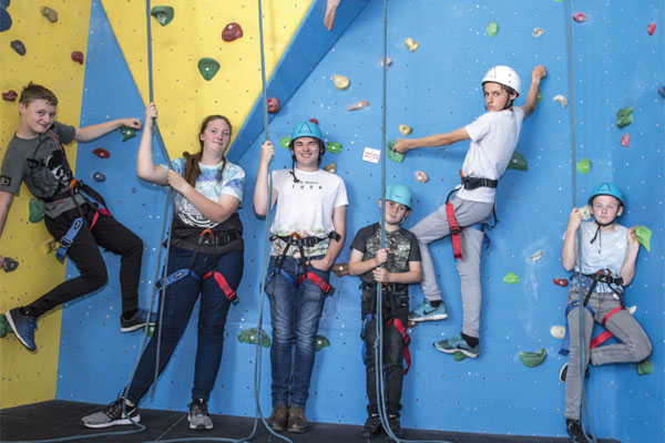 Six children and young people on a climbing wall in North Yorkshire.