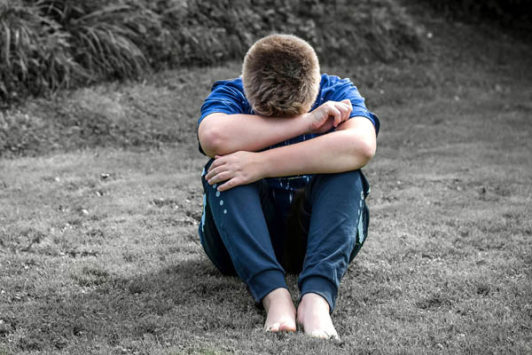A young boy resting his head on his arms representing children's mental health in North Yorkshire.
