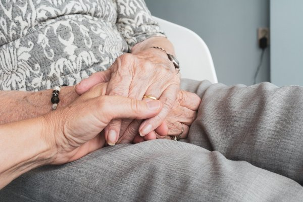 A woman holding the hand of an elderly person.