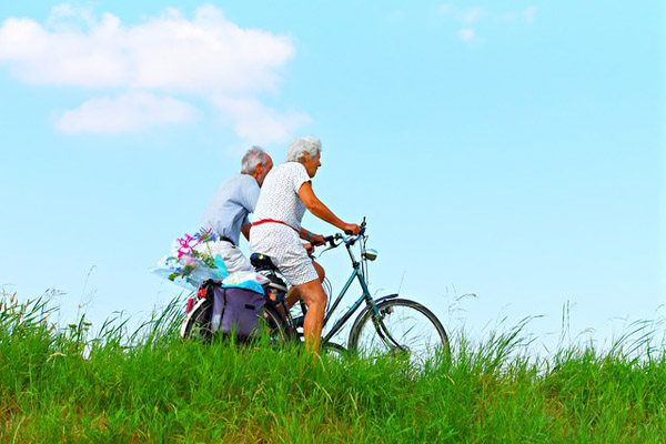 Two elderly people riding bicycles in the countryside.