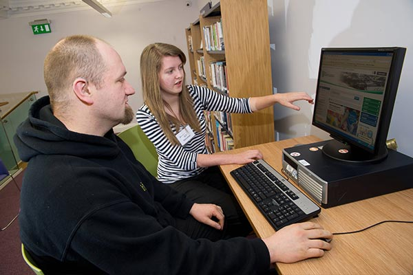 A man being shown how to access the internet on a North Yorkshire County Council computer by a librarian
