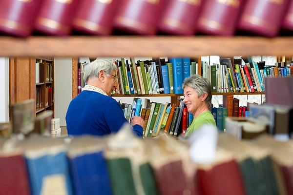 Two people standing and talking about books in a local library