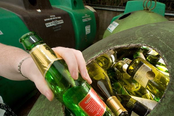 Glass bottles being placed into recycling bin