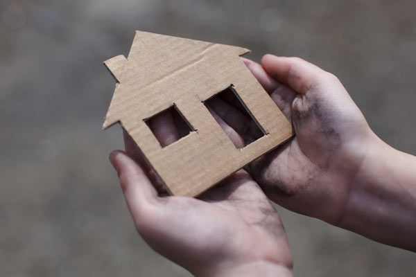Cardboard house held in a persons hands