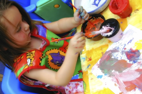 Child painting at North Yorkshire County Council childcare centre.