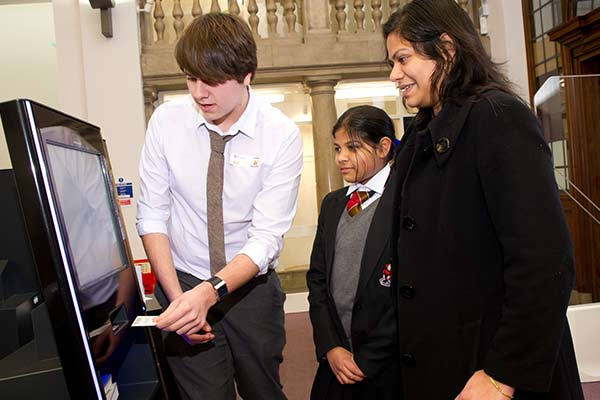 Library volunteers helps library users to renew books using a self-service machine