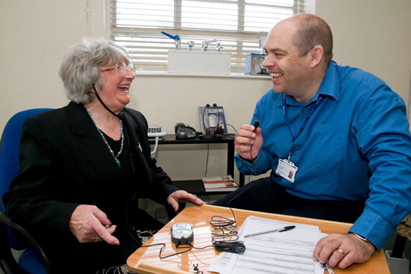 Older woman using a hearing aid system talking with a man in North Yorkshire.