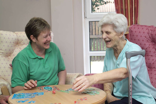 Older woman playing a game with her carer in North Yorkshire.