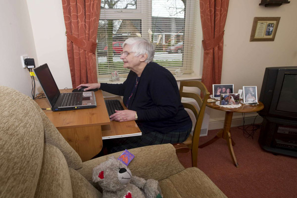 Older woman using a laptop in her flat in North Yorkshire.