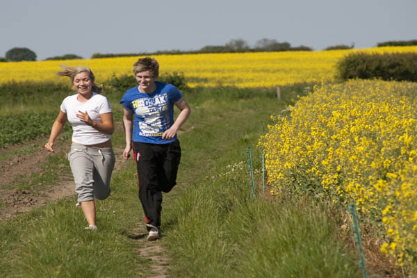 Two people running in a rapeseed field in North Yorkshire.