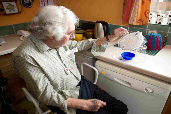 Older woman using a pouring device in her home in North Yorkshire.