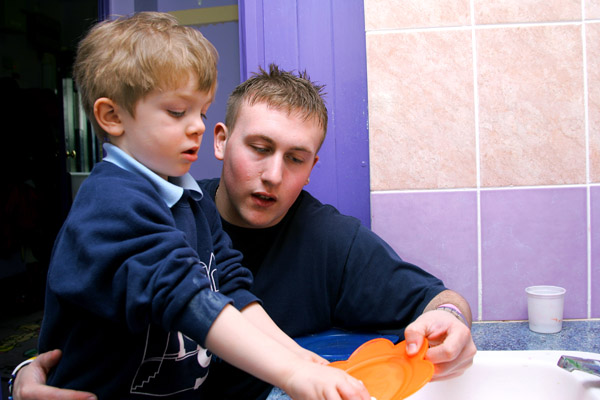 Teenage boy helping young boy in North Yorkshire.