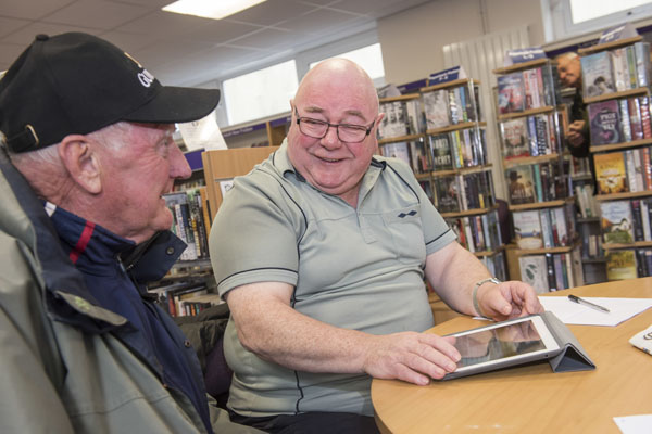 Volunteer helping a man use a tablet at Crosshills library in North Yorkshire.