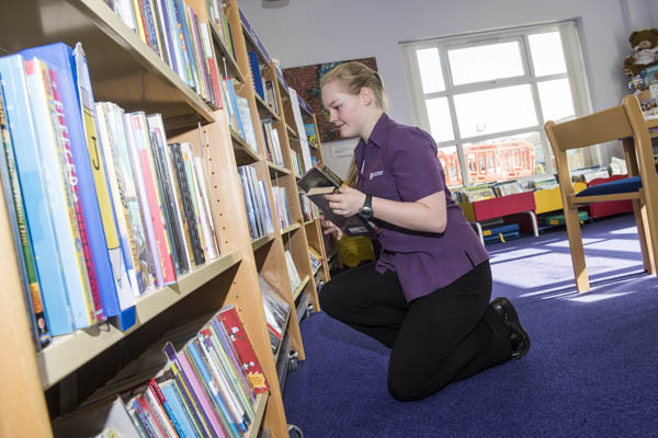 Volunteer reshelving books in Eastfield library in North Yorkshire.