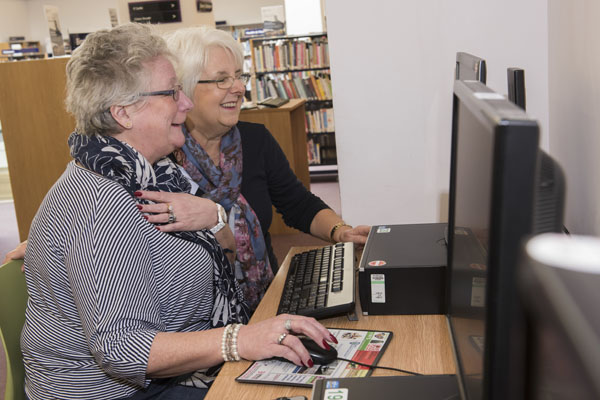 Volunteer helping a woman use a computer at a library in North Yorkshire.