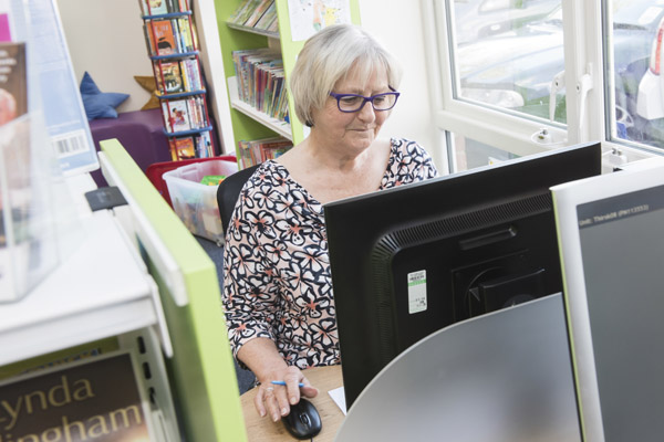 Woman using a computer in a library in North Yorkshire.