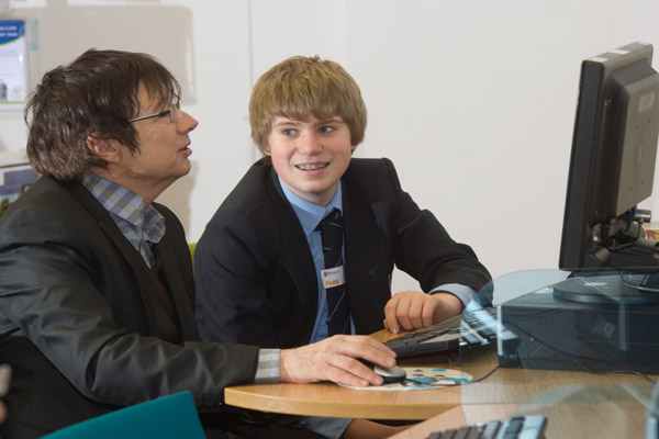 Volunteer helping a man use a computer at a library in North Yorkshire.