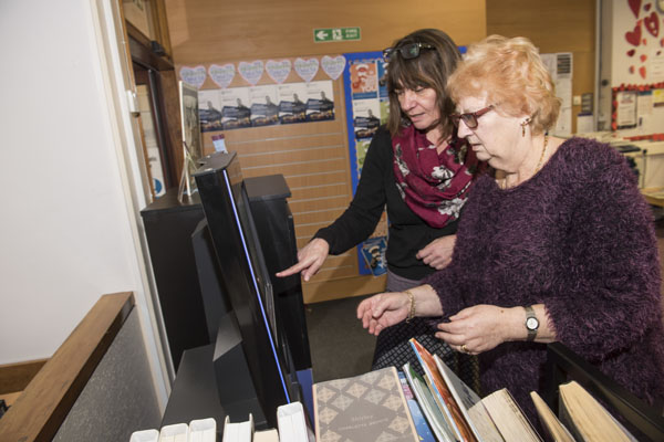 Volunteer helping a woman check out a book in a library in North Yorkshire.