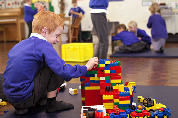 Primary school pupil playing with construction blocks