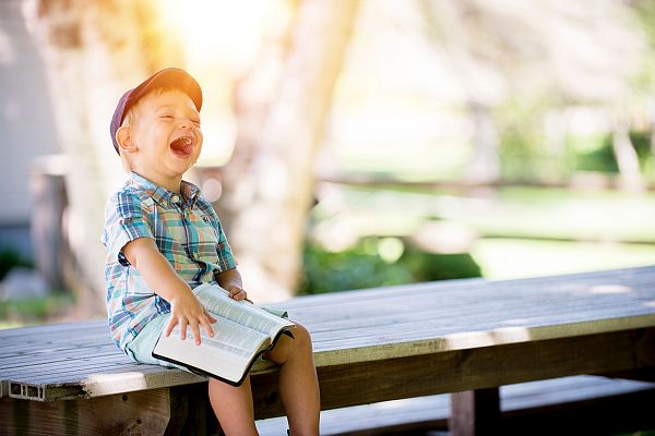 Young boy smiling on a bench.