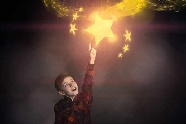 A young boy pointing up at a glittering star