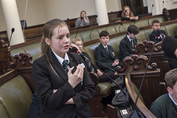 Girl speaking at youth event in council chamber.