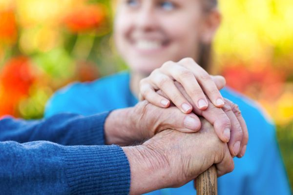Carer holding elderly persons hand.
