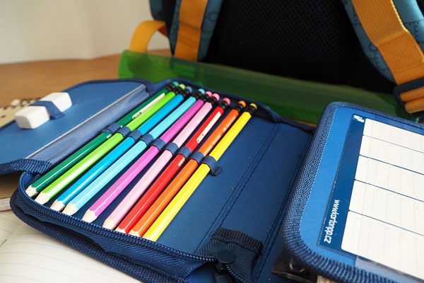 Pencil case containing coloured crayons and a rubber, and part of a backpack is also visible.